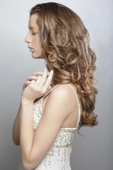 Jeune femme aux longs cheveux bouclés