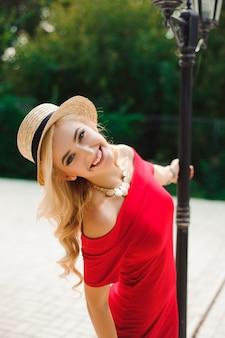 Jeune femme aux longs cheveux brillants posant avec plaisir tout en marchant à l'extérieur de bonne humeur