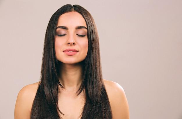 Jeune femme aux longs cheveux noirs posant. beau modèle gai garder les yeux fermés. calme et paisible.