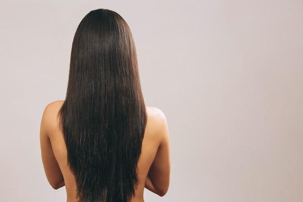Jeune femme aux longs cheveux noirs posant debout vue arrière