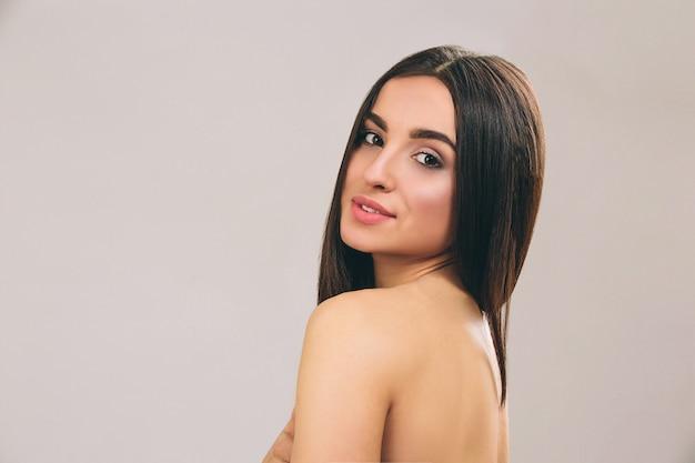 Jeune femme aux longs cheveux noirs posant. regarder droit et sourire. cheveux lisses. beau modèle.
