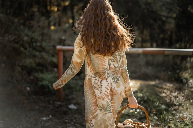 Jeune femme aux longs cheveux roux vêtue d'une robe en lin cueillant des champignons dans la forêt