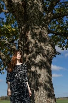 Jeune femme aux longs cheveux roux vêtue d'une robe en lin dans un endroit naturel sur le fond
