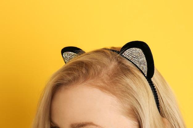 Jeune femme aux oreilles de chat sur fond de couleur, gros plan