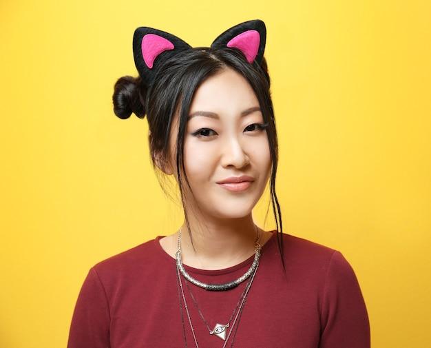 Jeune femme aux oreilles de chat sur fond de couleur