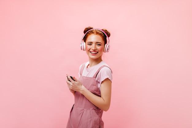 Jeune femme aux petits pains regarde l'écran du téléphone avec surprise. femme en robe et t-shirt blanc écoute de la musique avec des écouteurs sur fond rose.