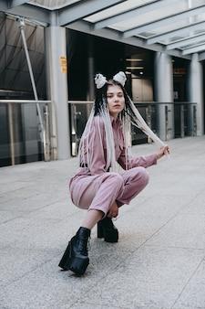 Jeune femme aux regards futuristes fille avec des dreadlocks noirs et blancs ou des tresses dans le contexte d'un bâtiment futuriste