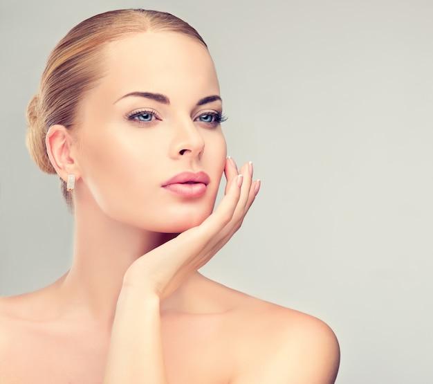 Une jeune femme aux yeux bleus et attrayante dans un maquillage expressif et un rouge à lèvres rose sur les lèvres touche tendrement son propre visage. regard brumeux. beauté, cosmétologie de maquillage.