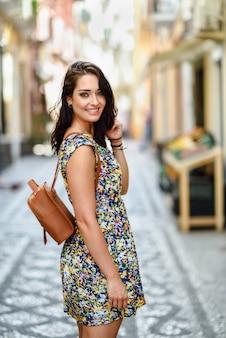 Jeune femme aux yeux bleus avec des cheveux ondulés bruns à l'extérieur