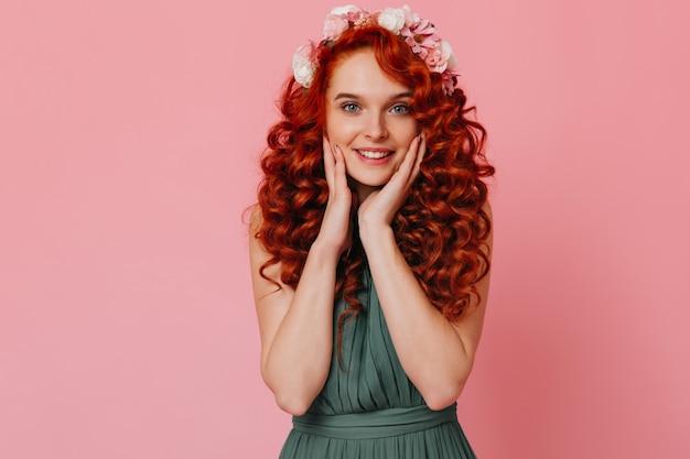 Jeune femme aux yeux bleus avec une couronne de fleurs regarde la caméra avec étonnement contre l'espace rose.
