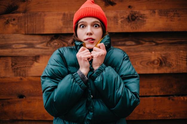 Jeune femme aux yeux bruns effrayée en regardant l'avant