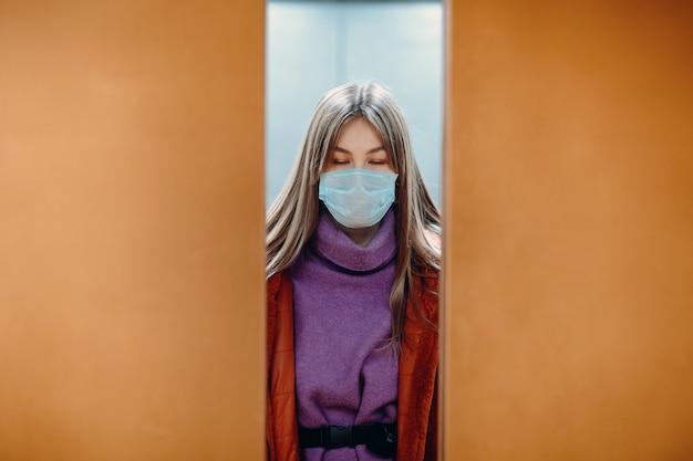 Jeune femme aux yeux fermés, debout dans l'ascenseur en masque médical. les portes se ferment. concept de pandémie de coronavirus covid-19.