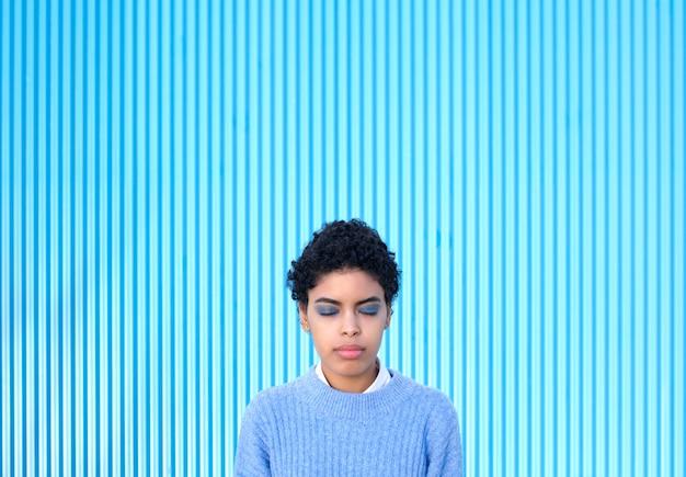 Jeune femme aux yeux fermés sur un mur bleu