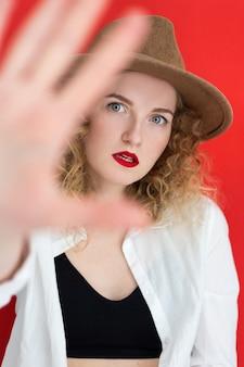 Jeune femme aux yeux verts portant un chapeau sur fond rouge. fille montrant le geste d'arrêt. concept des droits des femmes