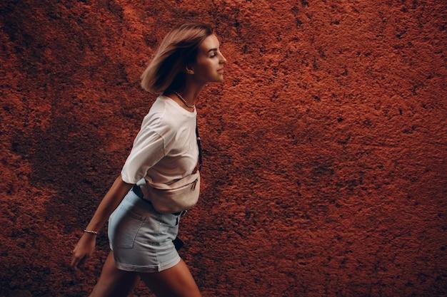 La jeune femme avance délibérément. fille en tissu décontracté marchant contre le mur de pierre rouge à marrakech, maroc