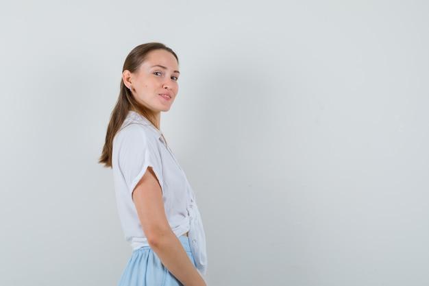 Jeune femme à l'avant en chemisier et jupe et à la charmante