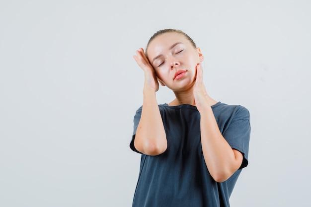 Jeune femme ayant mal de tête et frottant les tempes en t-shirt gris et à la fatigue