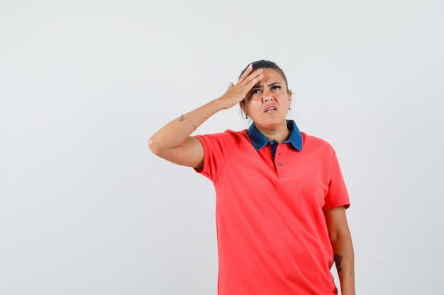 Jeune femme ayant mal à la tête en t-shirt rouge et lunettes et à la pensif. vue de face.