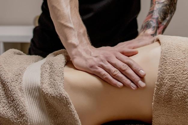 Jeune femme ayant un massage de l'abdomen. masseur fait un massage pour l'estomac.