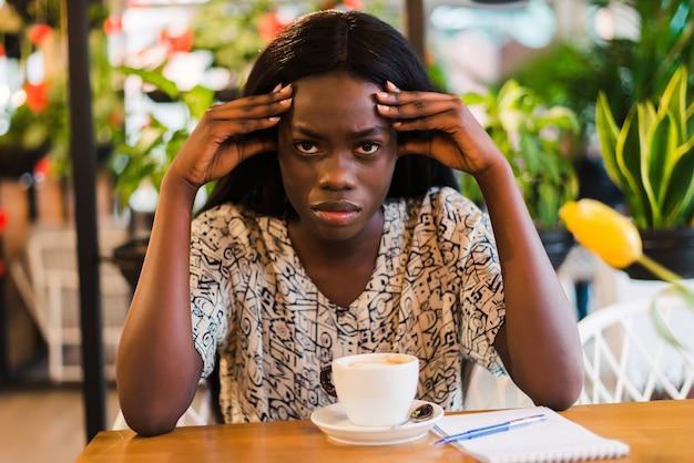 Jeune femme ayant des maux de tête tout en travaillant sur un ordinateur portable au café