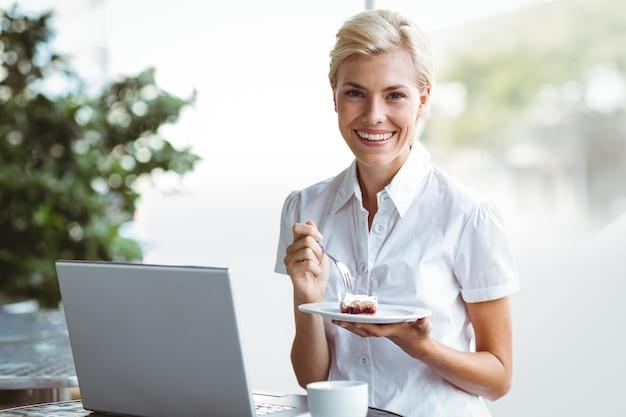 Jeune femme ayant un morceau de tarte à l'aide d'un ordinateur portable