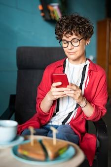 Jeune femme ayant pause au café - assis dans un fauteuil en face de la table servie et défilement dans le smartphone