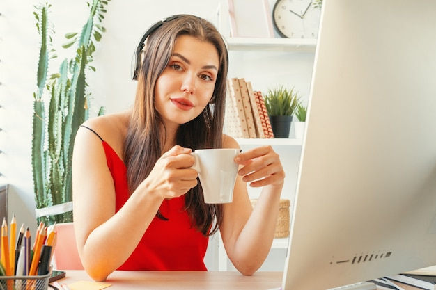 Jeune femme ayant une pause-café dans son bureau