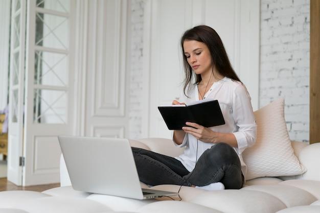 Jeune femme ayant une réunion d'affaires en ligne sur son ordinateur portable
