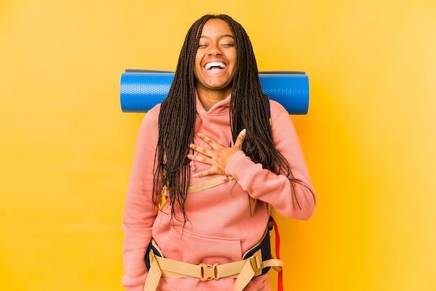 Jeune femme backpacker afro-américaine isolée rit à haute voix en gardant la main sur la poitrine.