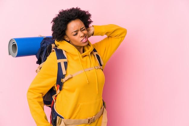 Jeune Femme Backpacker Afro-américaine Isolée Toucher L'arrière De La Tête, Penser Et Faire Un Choix. Photo Premium