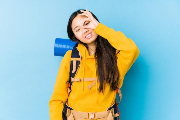 Jeune femme backpacker chinois excité en gardant le geste ok sur les yeux.