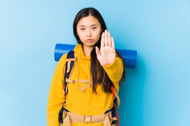 Jeune femme backpacker chinois isolé debout avec la main tendue montrant le panneau d'arrêt, vous empêchant.