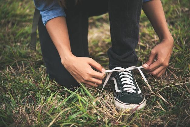 Jeune femme backpacker tout nouage lacets de chaussures de randonnée vont à la forêt.