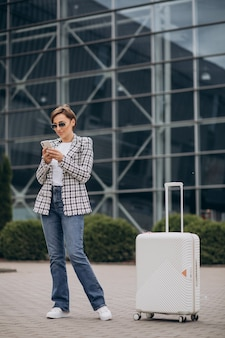 Jeune femme avec des bagages à l'aéroport voyageant et parlant au téléphone