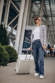 Jeune femme avec des bagages à l'aéroport voyageant