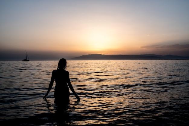 Jeune femme, baignade, dans, les, mer, dans, a, coucher soleil
