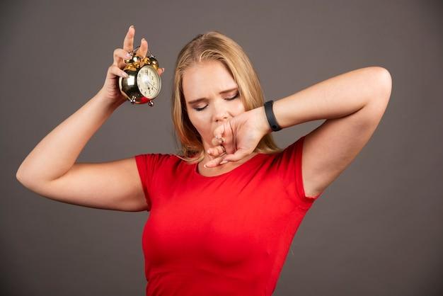 Jeune femme bâillant sur un mur noir avec horloge.