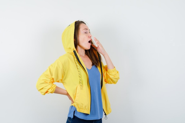 Jeune femme bâillant en t-shirt, veste et semblant endormie