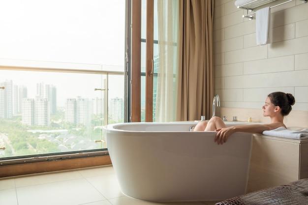 Jeune femme sur un bain blanc dans une salle de bains de luxe avec vue sur la ville