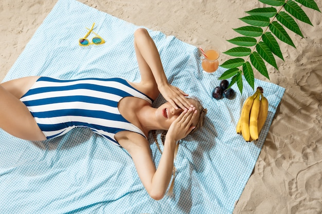 Jeune, femme, bains de soleil, rayé, maillot de bain
