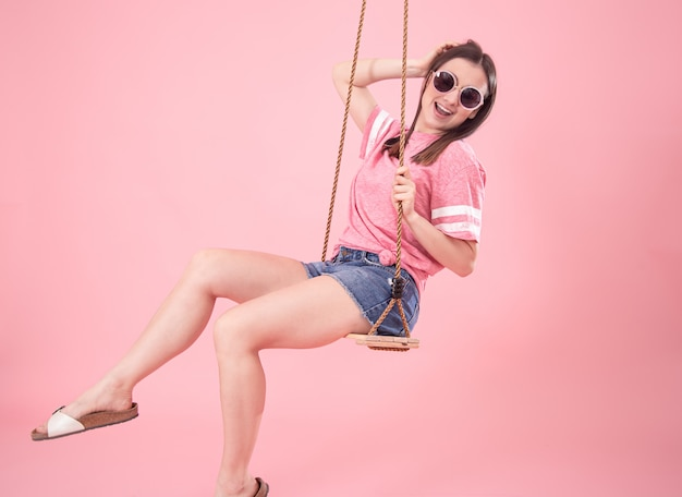 Jeune femme sur une balançoire sur une surface rose