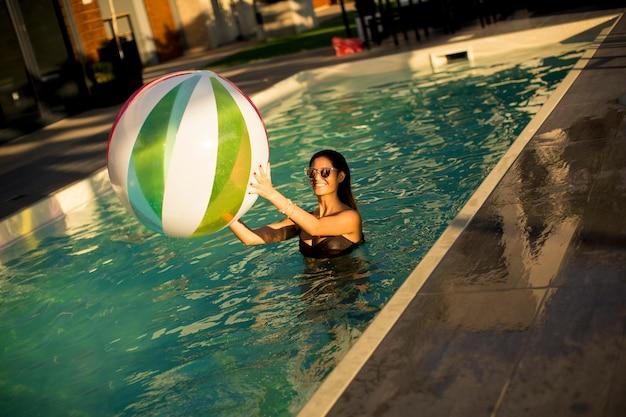 Jeune femme avec ballon dans la piscine