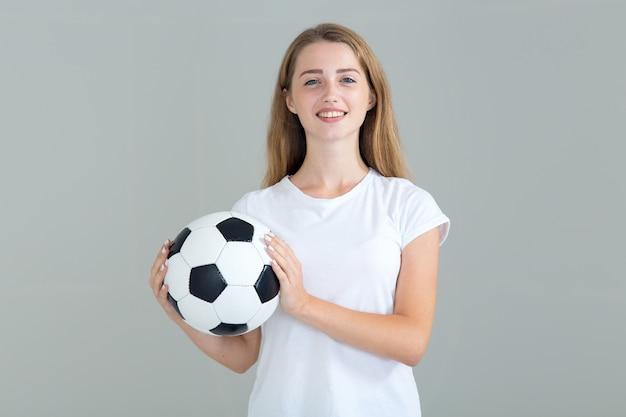 Jeune femme avec un ballon de soccer dans ses mains, isolé sur fond gris