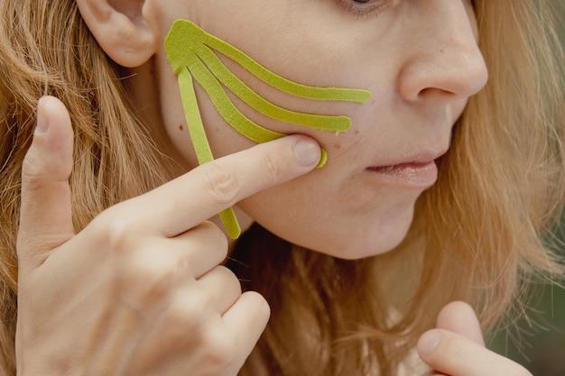 Jeune femme avec des bandes vertes sur le visage taping esthétique du visage