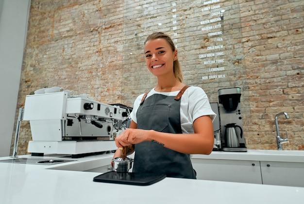 Jeune femme barista appuie sur le café moulu à l'aide de tamper in coffee shop.