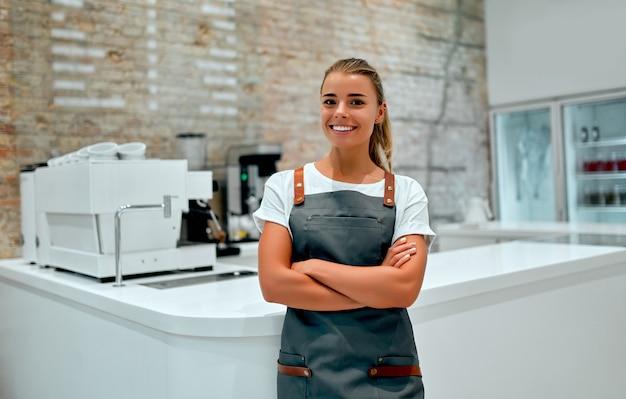 Jeune femme barista se tient au comptoir dans un café et sourit.