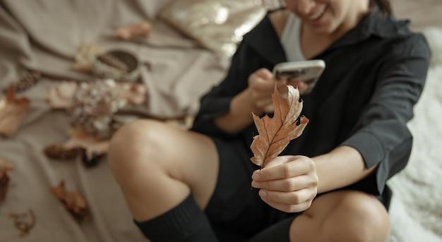 Une jeune femme en bas tricotés utilise le téléphone dans un lit douillet, au milieu des feuilles d'automne.