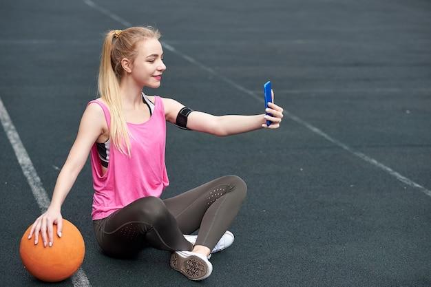 Jeune femme avec basket-ball à l'aide de téléphone après l'entraînement, faisant selfie.