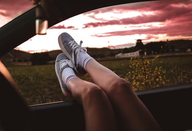 Jeune femme avec des baskets avec des pieds calés sur la fenêtre de la voiture au coucher du soleil