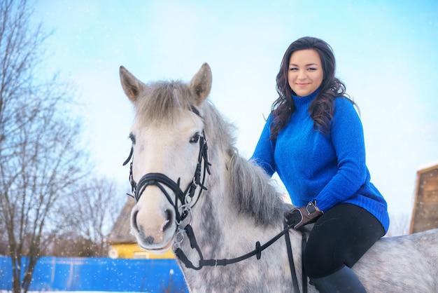 Une jeune femme avec un beau cheval blanc d'hiver